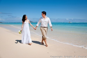 Asian bride and groom stroll with flower bouquet through sand and waves on Lanikai beach, Kailua, Hawaii