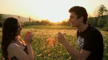stock-footage-cute-young-couple-blowing-dandelions-laughing-sunset-summer-field-hd
