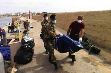 The body of a drowned passenger who was aboard a boat loaded with African migrants is brought ashore on the Italian island of Lampedusa. (Claudio Peri / European Pressphoto Agency)