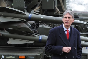 Defence Secretary Philip Hammond stands in front of his very hard military force.